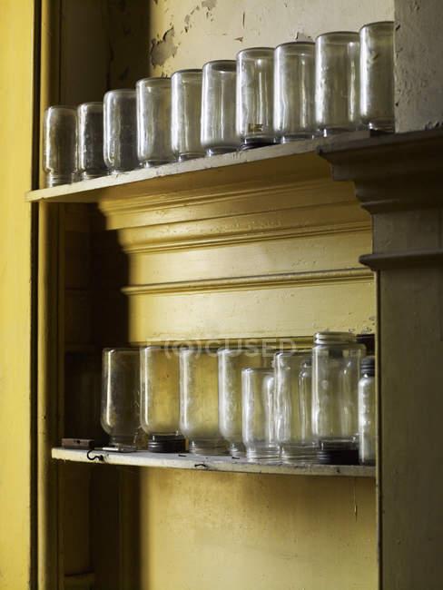 Scaffali stoccaggio vasetti di vetro rovesciato — Foto stock
