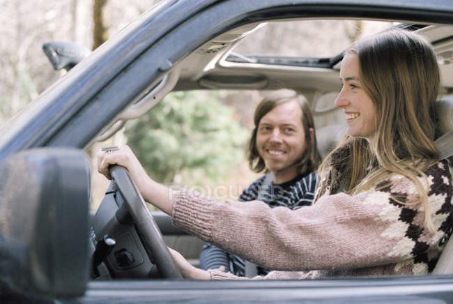 Smiling young couple driving in car. — Stock Photo