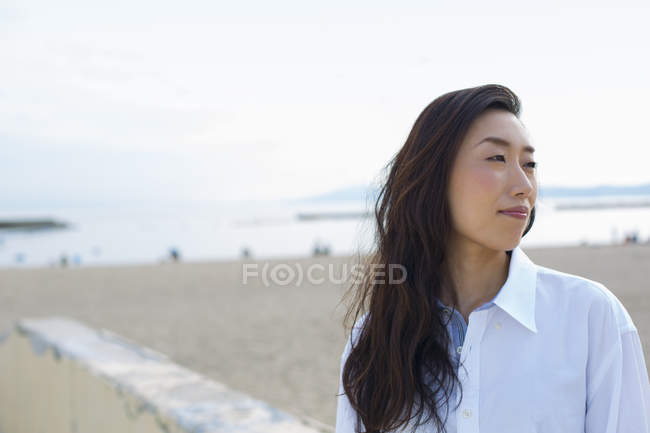Mujer asiática en una playa - foto de stock