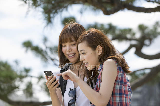 Japanese friends listening to music — Stock Photo
