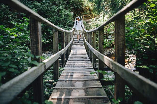 Homme marchant à travers le pont — Photo de stock