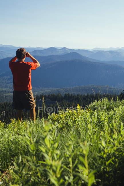 Uomo in piedi su un crinale di montagna — Foto stock