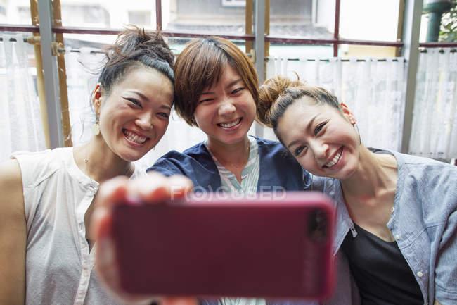 Drei Frauen, die an ein Handy — Stockfoto