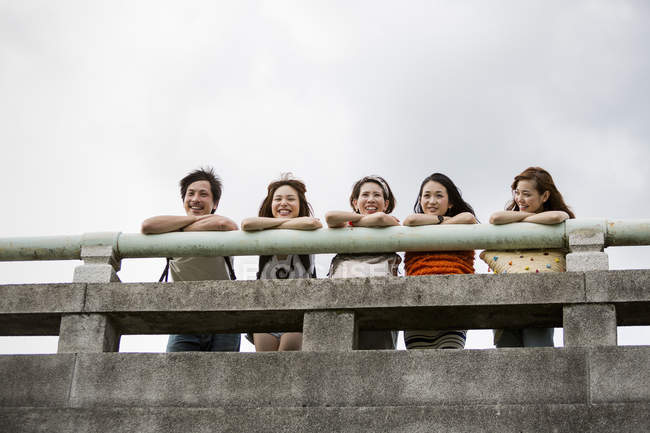 Friends in the park leaning on a parapet. — Stock Photo