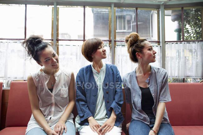 Drei Frauen sitzen drinnen wegschauen — Stockfoto