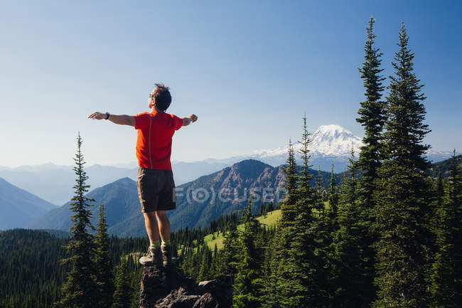 Male hiker standing with arms outstretched — Stock Photo