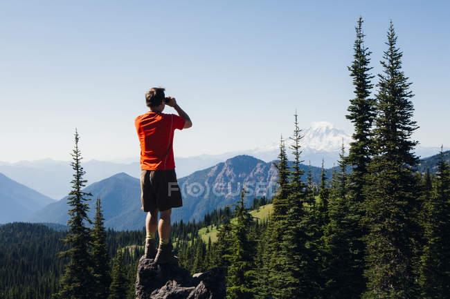 Hombre de pie en una cresta de montaña - foto de stock