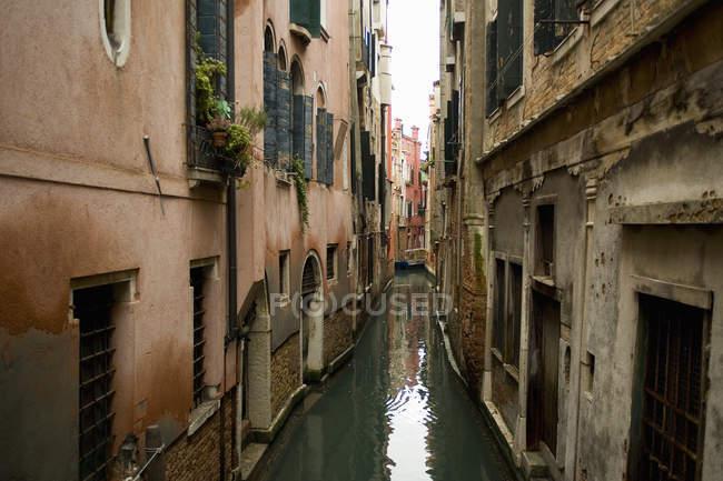 Canal estrecho con edificios históricos - foto de stock