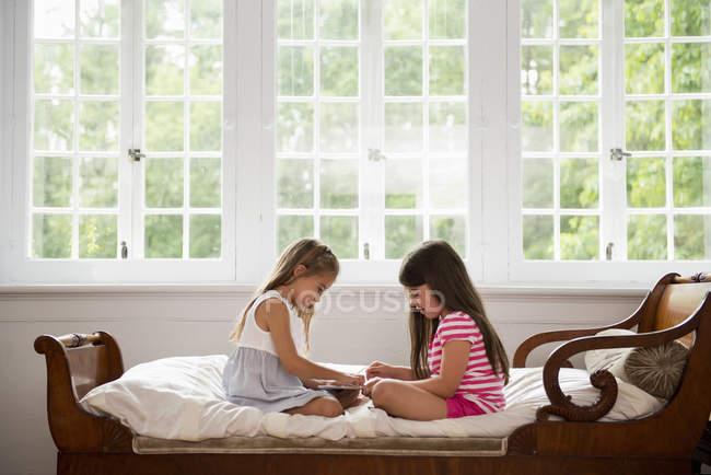 Сестры с помощью цифрового планшета . — стоковое фото