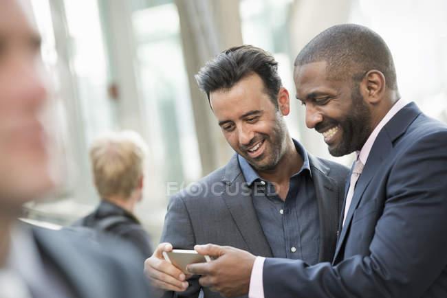 Hombres de negocios revisando un teléfono inteligente . - foto de stock