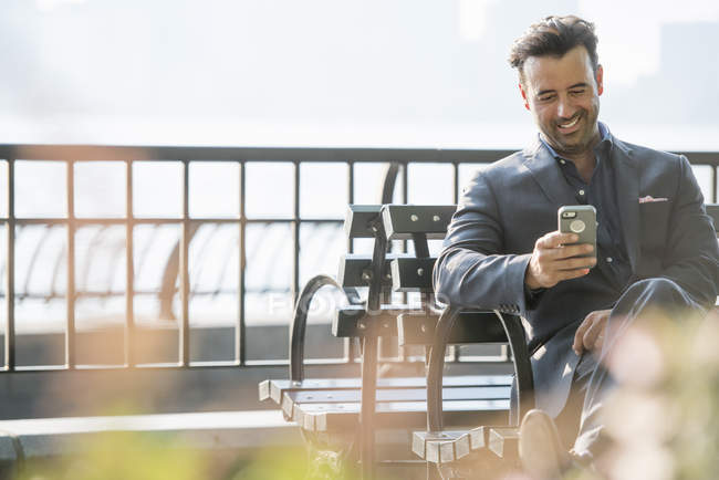 Businessman seated checking his phone — Stock Photo