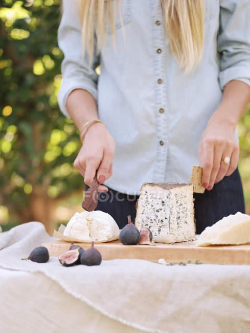 Mulher corte de queijo na mesa — Fotografia de Stock