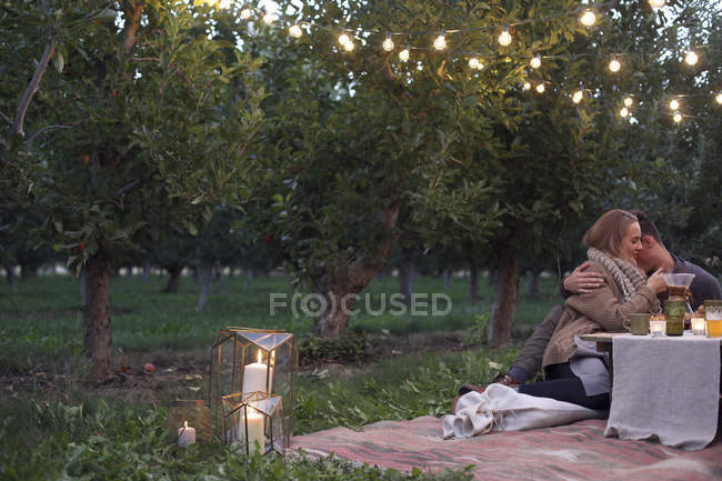Couple sitting on the ground in Apple orchard — Stock Photo