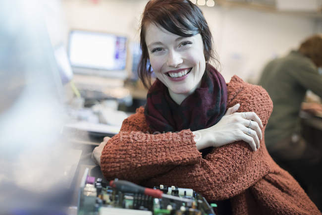 Donna appoggiata a un banco da lavoro . — Foto stock