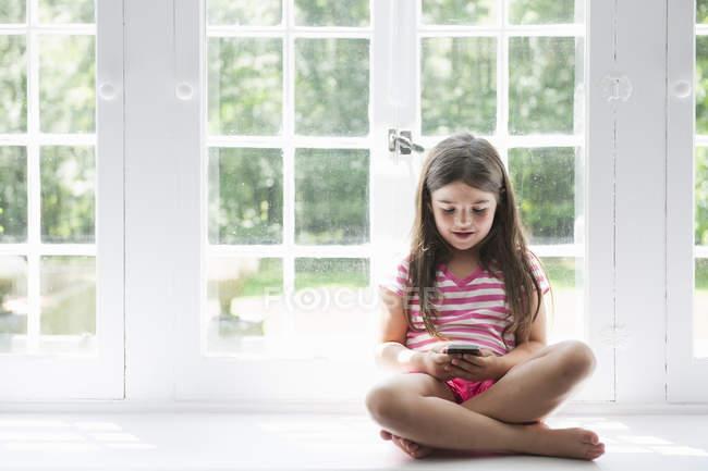 Menina segurando um telefone inteligente. — Fotografia de Stock