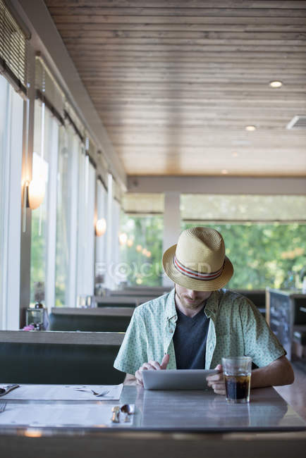 Man using a digital tablet sitting in a diner — Stock Photo