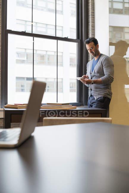 Indian businessman checking smart phone. — Stock Photo