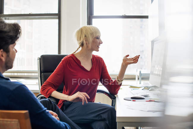 Man and woman in an office talking — Stock Photo
