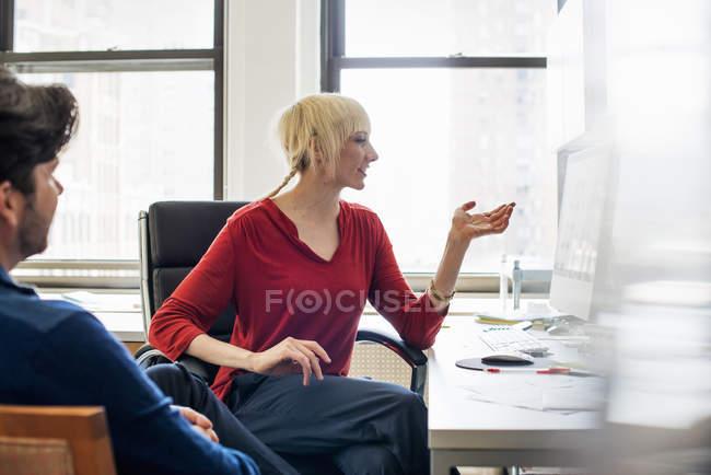 Чоловік і жінка в офісі говорити — стокове фото