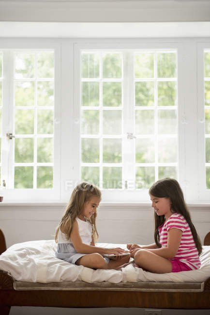 Girls playing with digital tablet. — Stock Photo