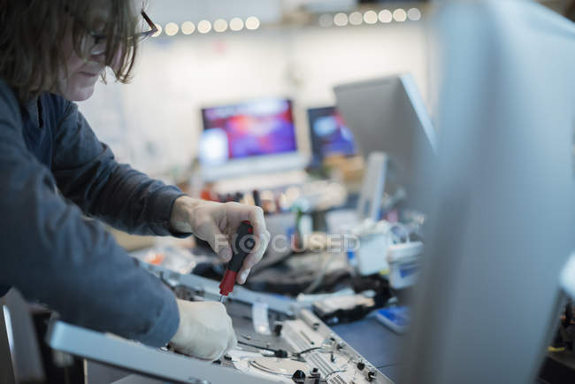 Man using a screwdriver on the circuit boards — Stock Photo