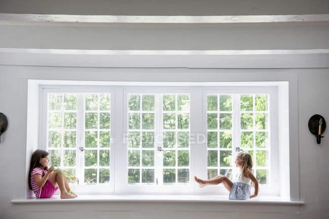 Niñas jugando por una ventana grande . - foto de stock