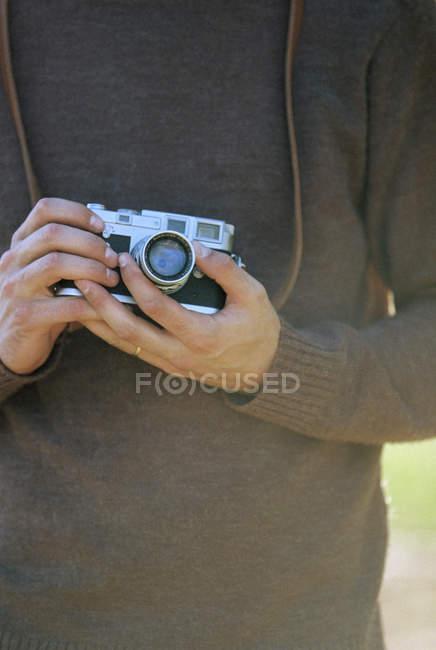 Homem segurando uma câmera vintage — Fotografia de Stock