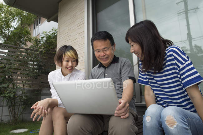 Man and two women outside house — Stock Photo