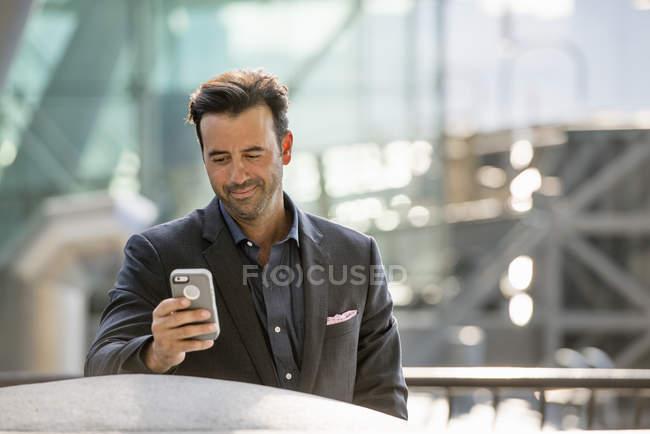 Homme d'affaires vérifiant son téléphone intelligent . — Photo de stock