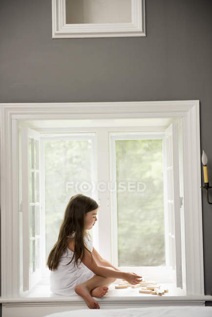 Menina em um vestido branco sentado por uma janela — Fotografia de Stock