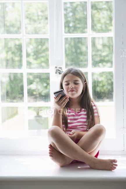 Дівчинка, граючи з смарт-телефон. — стокове фото