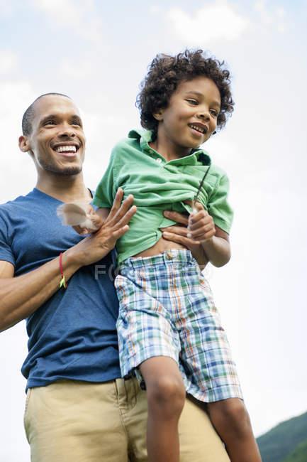 Мужчина, поднимающий сына на руки — стоковое фото