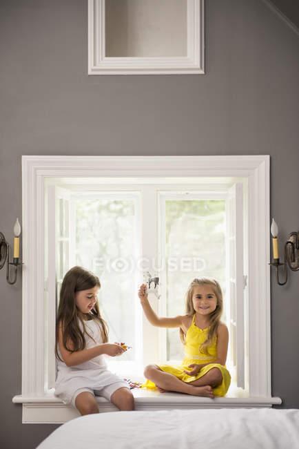 Meninas sentadas em um assento da janela — Fotografia de Stock