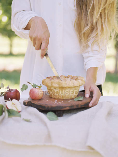 Femme coupant une tarte aux pommes — Photo de stock