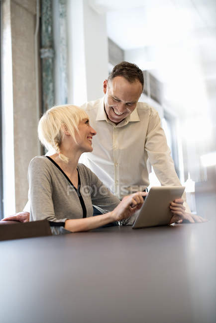 Pessoas que compartilham uma mesa digital em um escritório — Fotografia de Stock