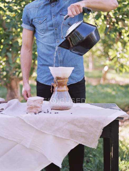 Man standing at a table, making coffee. — Stock Photo
