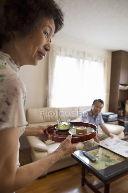 Woman serving tray of food — Stock Photo