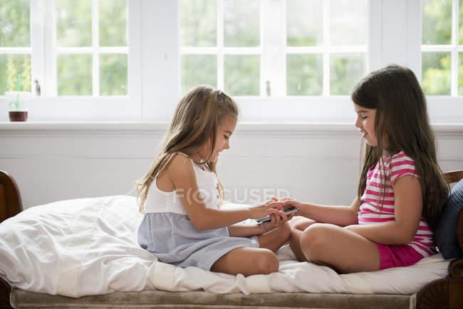 Girls holding a smart phone — Stock Photo