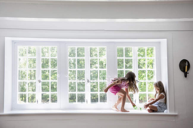 Sisters playing by a large window. — Stock Photo