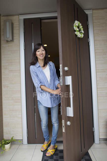 Woman standing at her front door. — Stock Photo