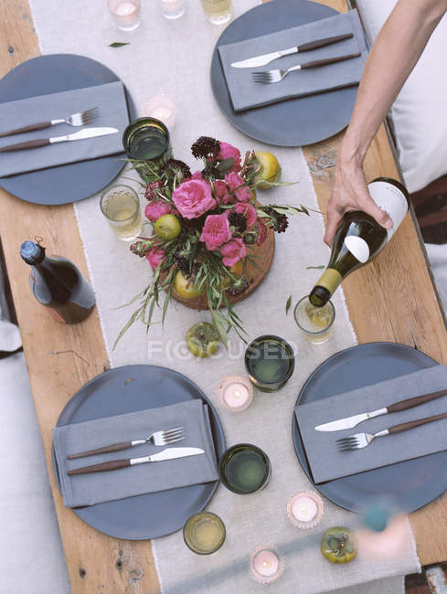 Table setting, a person pouring wine. — Photo de stock