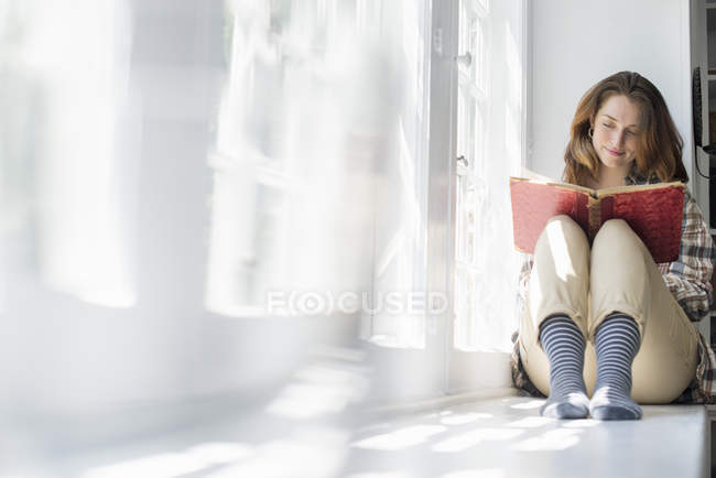 Woman seated by a window — Stock Photo