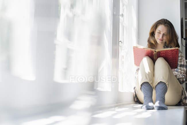 Женщина, сидящая у окна — стоковое фото