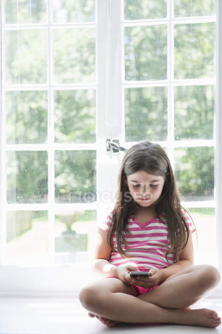 Girl playing with a smart phone. — Stock Photo