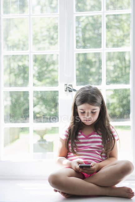 Девушка играет со смартфоном . — стоковое фото
