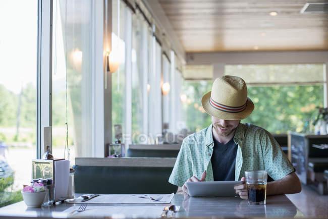Uomo in una tavola calda utilizzando un tablet digitale — Foto stock