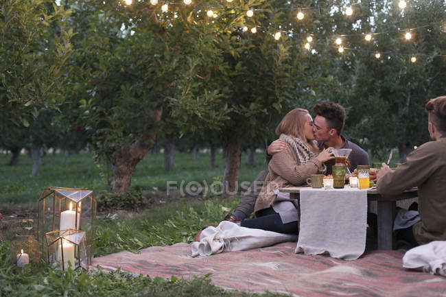 Couple sitting on the ground and kissing — Stock Photo