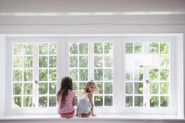 Сестры сидят у большого окна . — стоковое фото