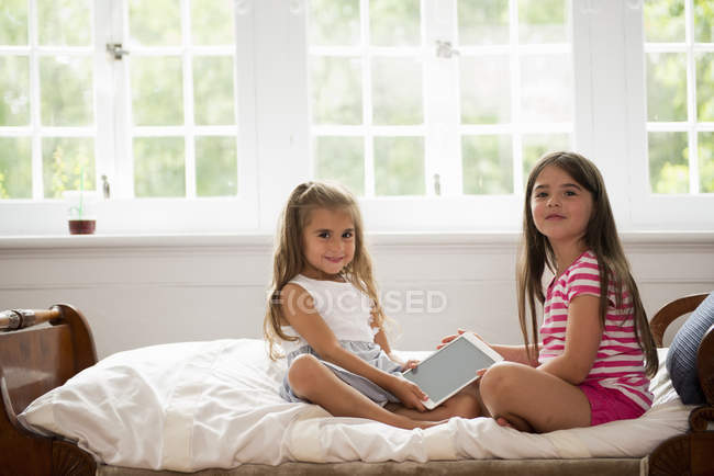 Girls holding a digital tablet. — Stock Photo