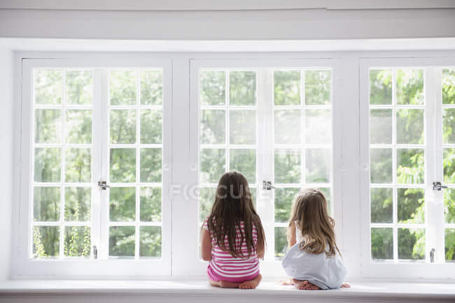 Two girls sitting by a large window. — Stockfoto